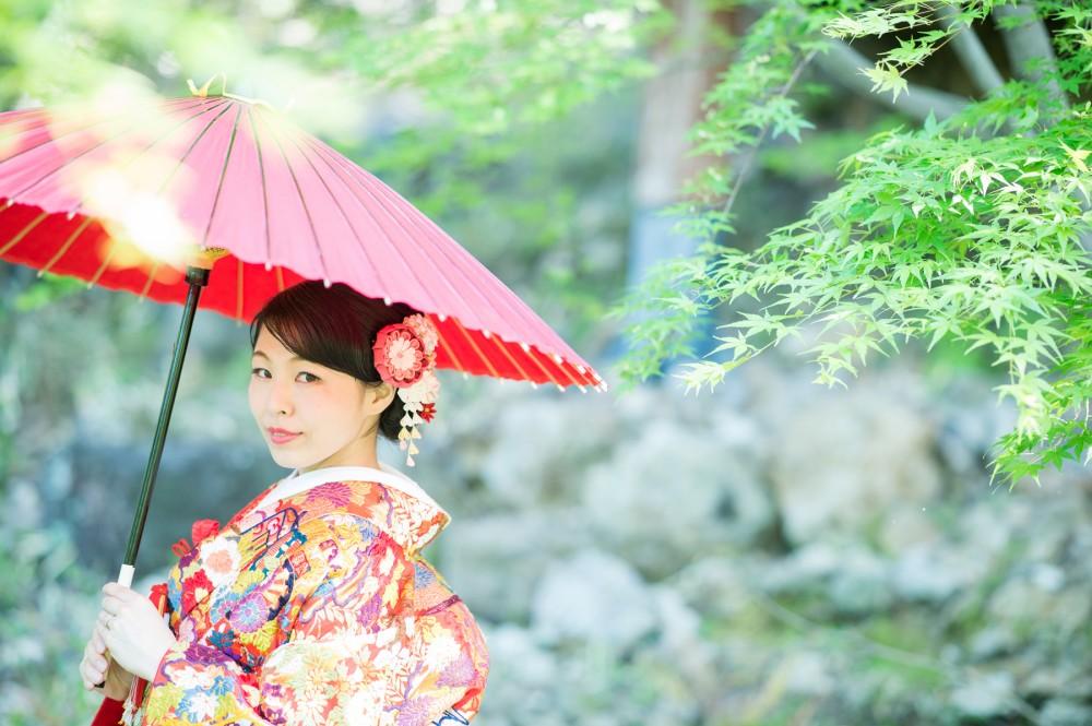 新緑で、赤い和傘を持つ花嫁