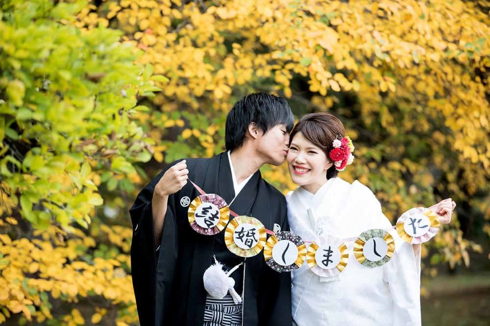 黄色くなった葉っぱの前で、結婚しましたのガーランドを使った写真