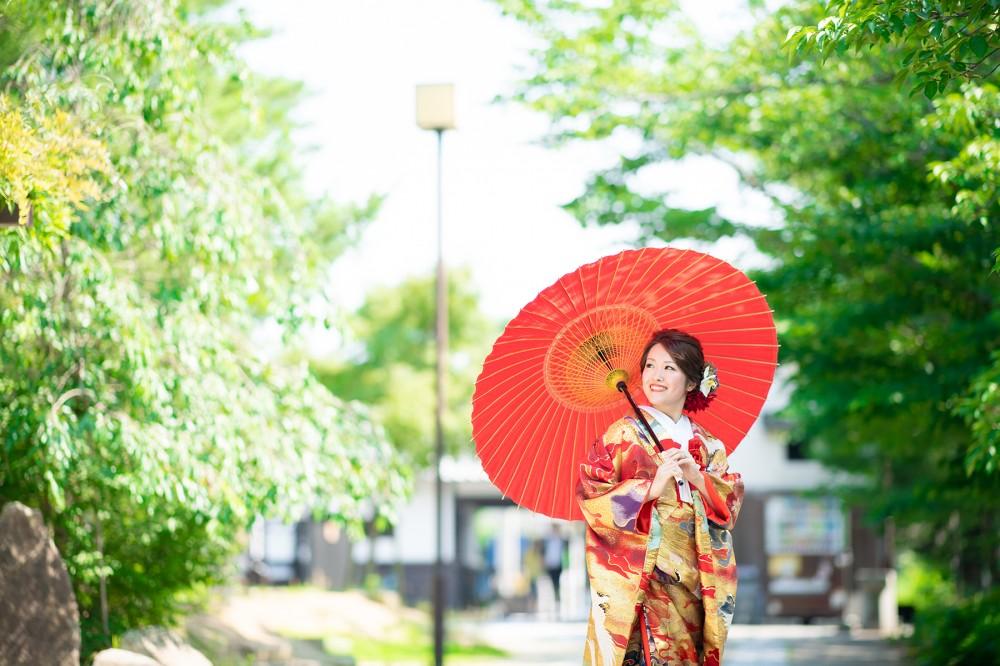 夏の日差し、和傘をさした色打掛姿の花嫁さん。