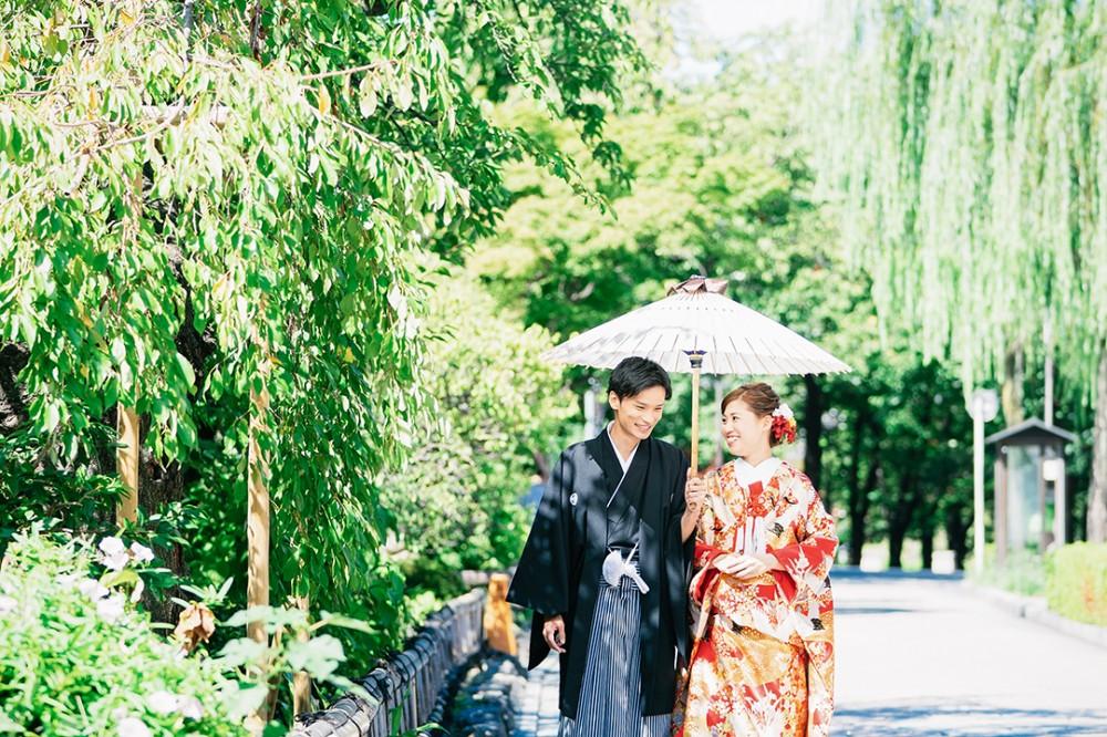 祇園白川で和装前撮りしている写真。白い和傘を持って歩いている雰囲気。