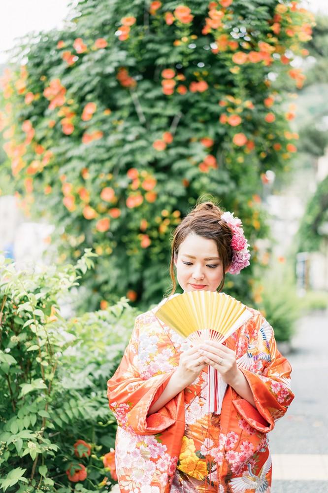 オレンジの花が背景の和装の新婦様ソロショット